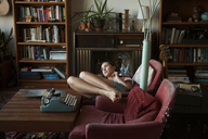 Thoughtful woman relaxing on arm chairs at home - CAVF08650