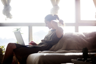 Woman using laptop computer while sitting on sofa by window at home - CAVF08668