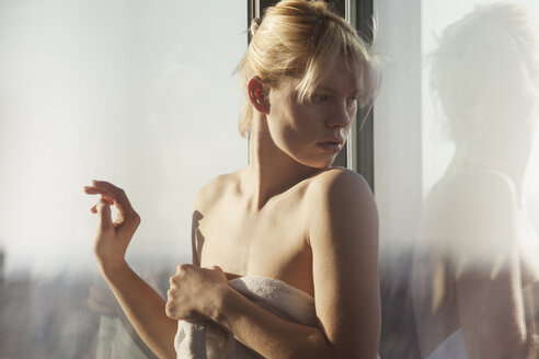 Surprised woman wrapped in towel looking over shoulder while standing by window - CAVF08686
