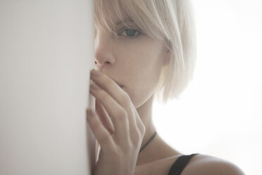 Portrait of woman hiding behind white wall at home - CAVF08692