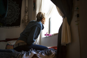 Side view of woman looking through window while sitting on bed at home - CAVF08695
