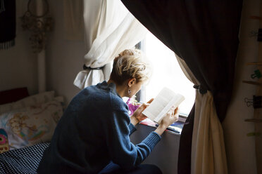 High angle view of woman reading book while sitting by window at home - CAVF08698