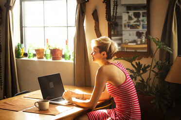 Woman with laptop computer looking away while sitting by table at home - CAVF08710
