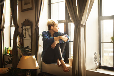 Woman looking away while sitting by window sill at home - CAVF08713