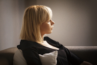 Woman looking away while sitting on sofa at home - CAVF08722