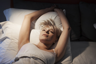High angle view of woman lying on bed at home - CAVF08731