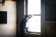 Side view of man in hat looking away while standing by window at home - CAVF08740