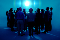 Crowd standing around bright light - CAIF16772