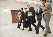 Judges and lawyers walking through courthouse together - CAIF16877