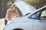 Woman checking car engine at roadside - CAIF16913