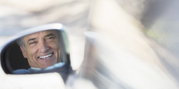 Reflection of smiling senior man in side-view car mirror - CAIF16931