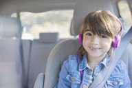 Portrait of smiling girl with headphones in back seat of car - CAIF16946