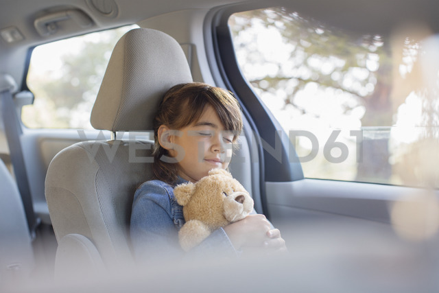 Girl with teddy bear sleeping in back seat of car - CAIF16949