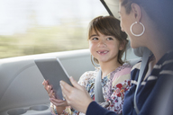 Happy mother and daughter using digital tablet in back seat of car - CAIF16958