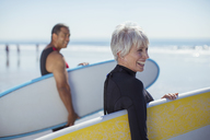 Senior couple carrying surfboards on beach - CAIF16991