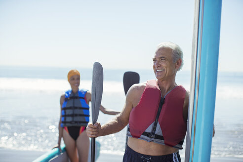 Senior couple with paddleboards on beach - CAIF16994