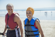 Enthusiastic couple in life jackets on beach - CAIF17006