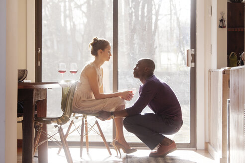 Man looking at woman sitting on chair by window at home - CAVF08815