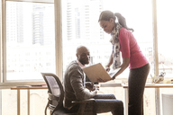 Businesswoman showing laptop to businessman at office - CAVF08950