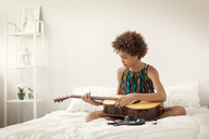 Girl playing guitar while sitting on bed at home - CAVF09007