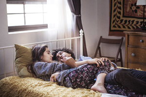 Couple lying on bed at home - CAVF09019