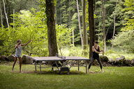 Couple playing table tennis in forest - CAVF09109