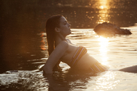Side view of woman in lake during sunrise - CAVF09130