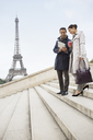 Business people talking on steps near Eiffel Tower, Paris, France - CAIF17010