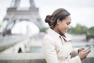 Businesswoman using cell phone near Eiffel Tower, Paris, France - CAIF17013