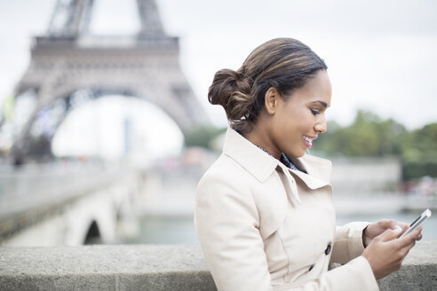 Businesswoman using cell phone near Eiffel Tower, Paris, France - CAIF17013