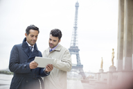Businessmen using digital tablet near Eiffel Tower, Paris, France - CAIF17016