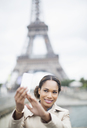 Woman taking self-portrait in front of Eiffel Tower, Paris, France - CAIF17037