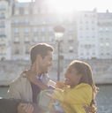 Man holding girlfriend along Seine River, Paris, France - CAIF17055