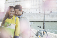 Couple with bouquet of flowers by Seine River, Paris, France - CAIF17067