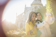 Women taking self-portrait in urban park - CAIF17070