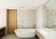 Stone walls behind soaking tub in modern bathroom - CAIF17100