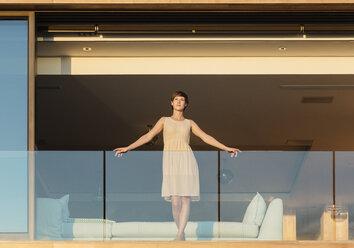 Woman standing on luxury balcony - CAIF17115