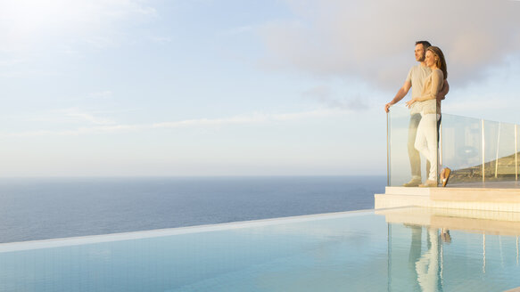 Couple overlooking ocean from modern balcony - CAIF17130
