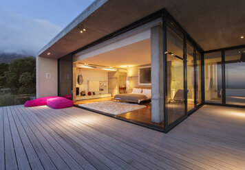 Sliding glass doors onto bedroom of modern house - CAIF17133