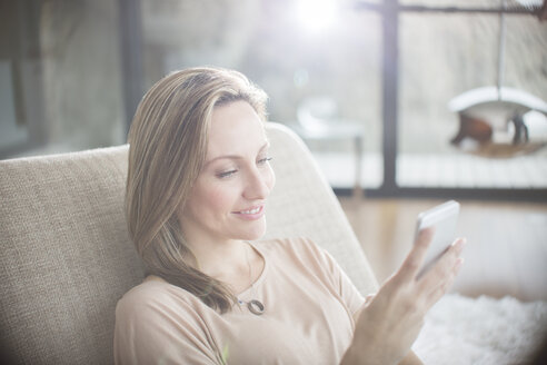 Woman using cell phone on sofa - CAIF17136