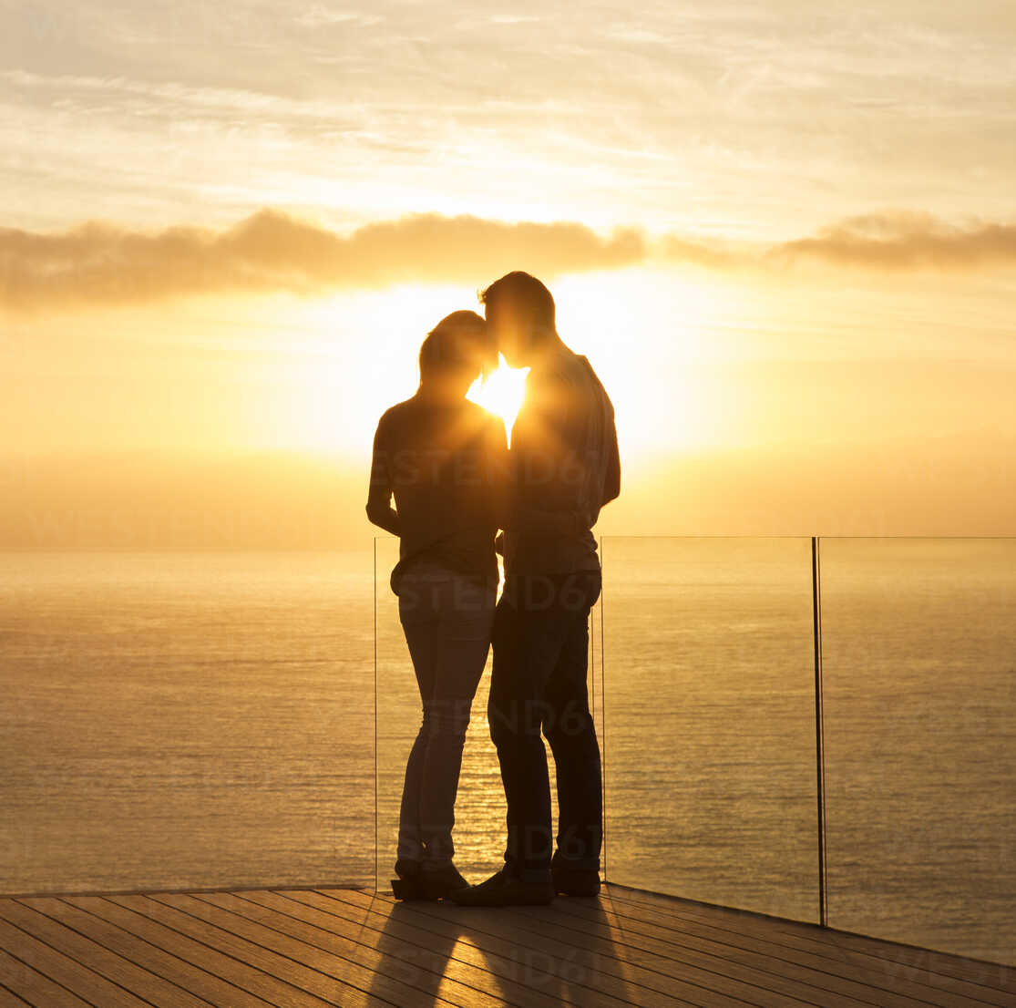 Silhouette of couple at sunset over ocean - CAIF17142 - Astronaut Images/Westend61