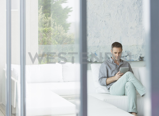 Man using digital tablet on sofa - CAIF17148 - Astronaut Images/Westend61
