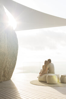 Couple relaxing together on modern balcony - CAIF17154