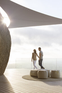 Couple walking on modern balcony - CAIF17160