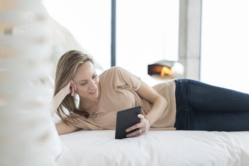 Woman using digital tablet on bed - CAIF17169
