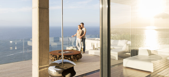 Couple on modern balcony overlooking ocean - CAIF17178