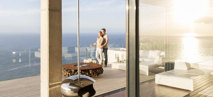 Couple on modern balcony overlooking ocean - CAIF17178