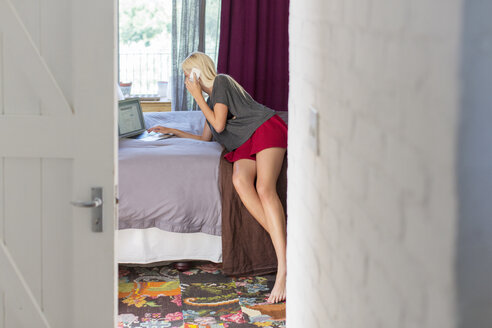 Woman talking on cell phone in bedroom - CAIF17199