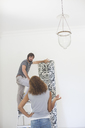 Couple deciding on wallpaper on wall - CAIF17224