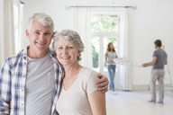 Older couple smiling together in living space - CAIF17236